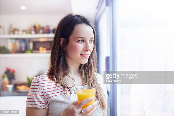 young woman looking out the window thinking - orange juice stock pictures, royalty-free photos & images
