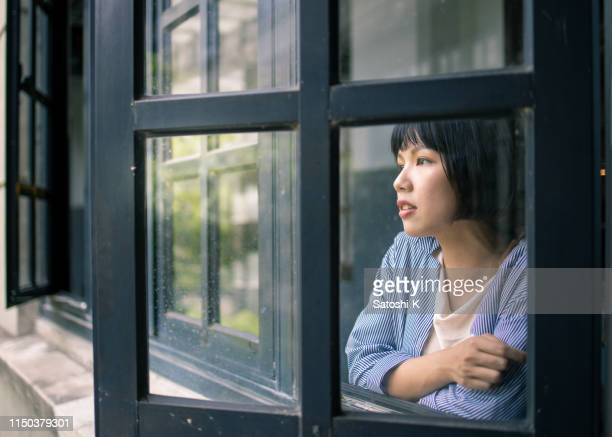 young woman looking out throug window from school building - cross processed stock pictures, royalty-free photos & images