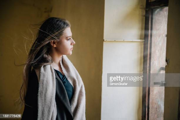 young woman looking out through window - moment of silence stock pictures, royalty-free photos & images