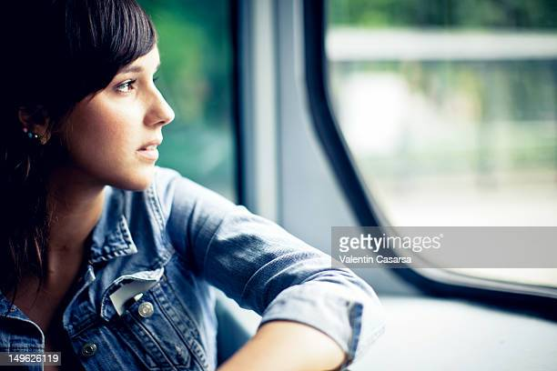 young woman looking out tram window - schwarzes haar stock-fotos und bilder