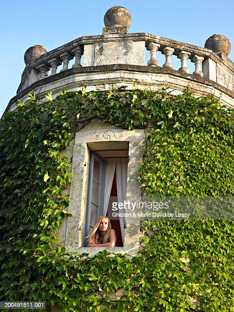 Young woman looking out window, building covered in ivy