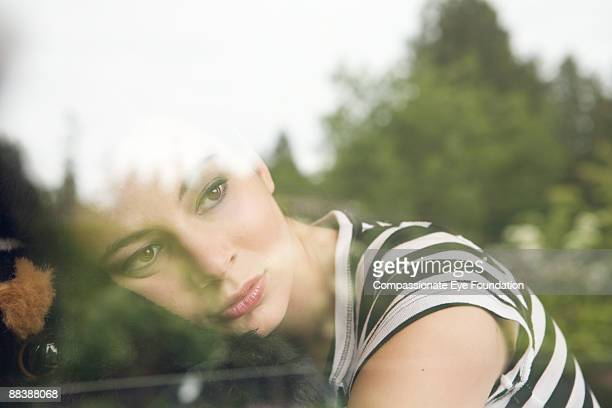 young woman looking out window