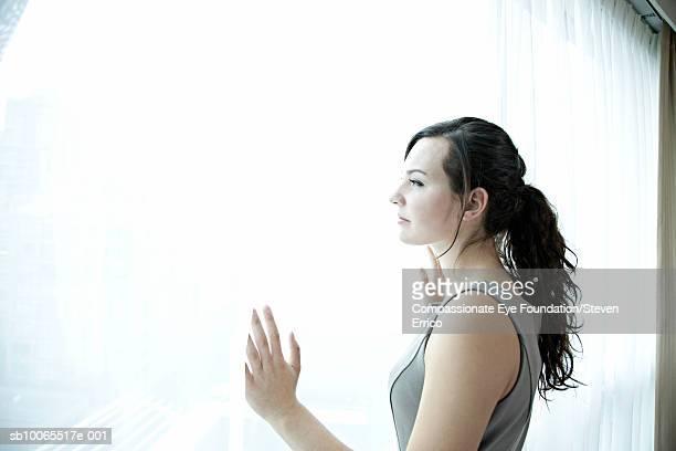 "young woman looking out window - ""compassionate eye"" - fotografias e filmes do acervo"