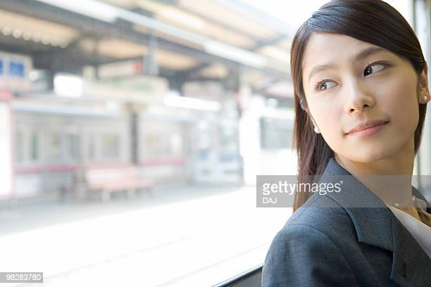 Young woman looking outside from the window, looking back