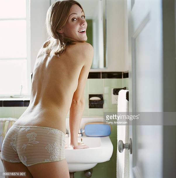 Young woman looking over shoulder in bathroom, portrait