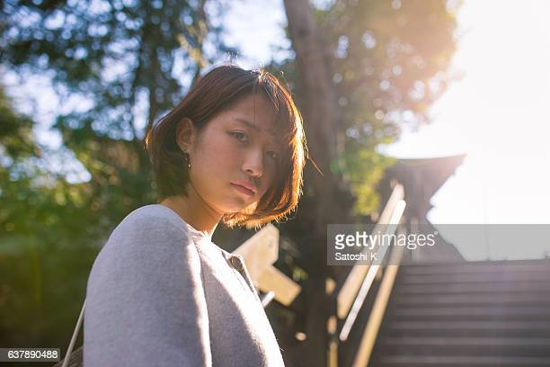 Young woman looking over shoulder in sunlight