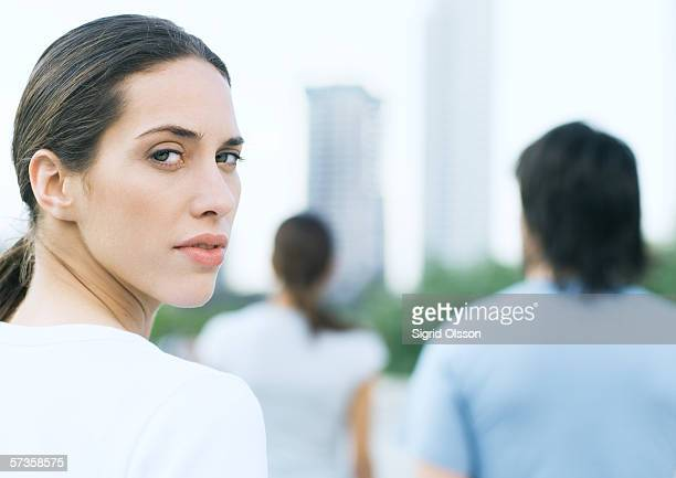 young woman looking over shoulder in urban park - assertiveness stock pictures, royalty-free photos & images