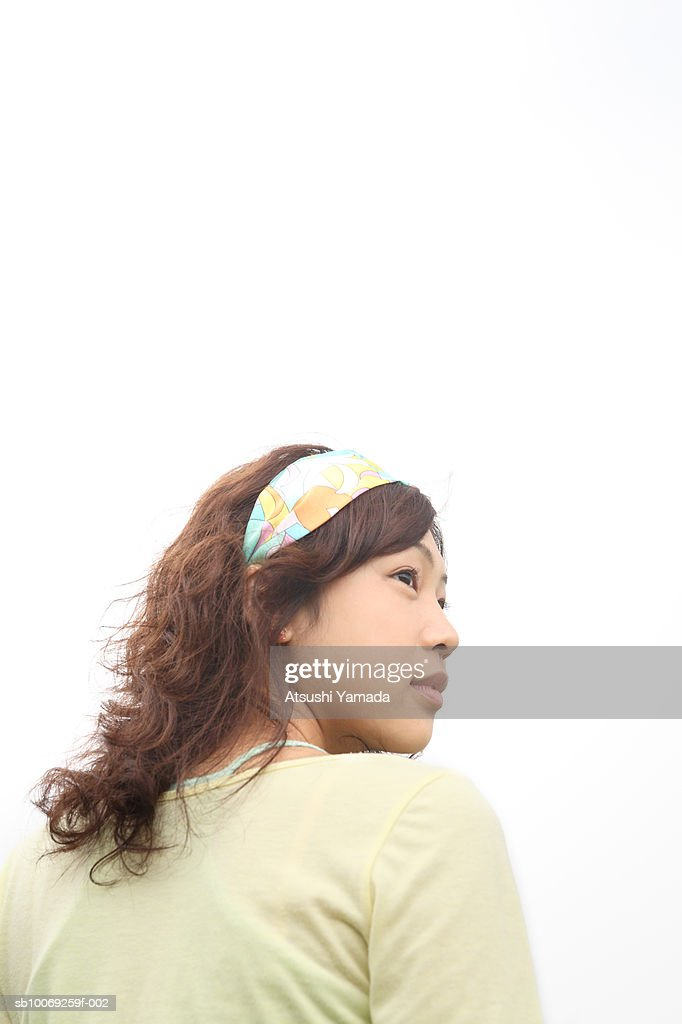 Young woman looking over shoulder, low angle view : Stockfoto