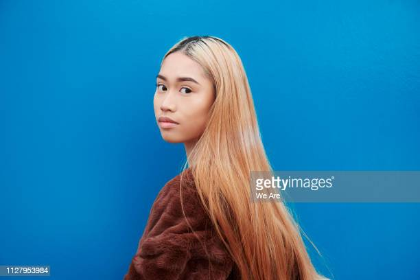 young woman looking over shoulder to camera. - generation z stock pictures, royalty-free photos & images