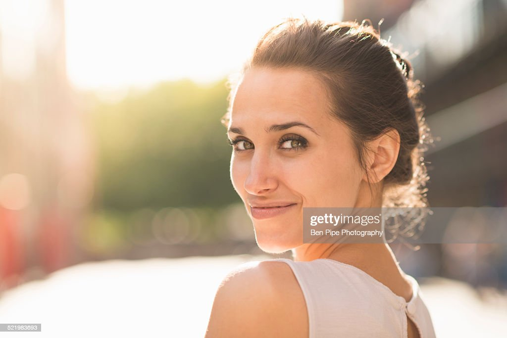 Young woman looking over shoulder towards camera : Stock Photo