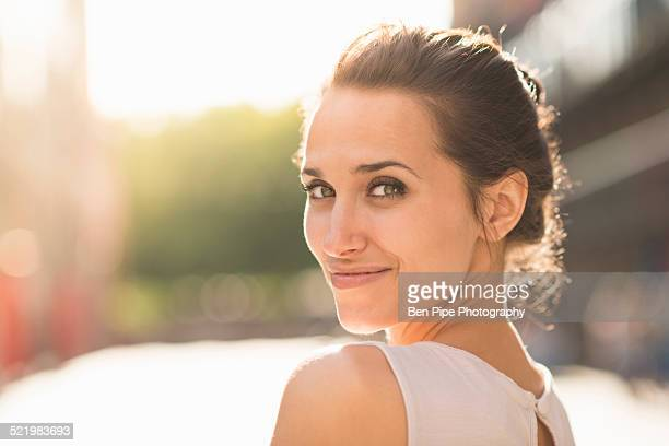young woman looking over shoulder towards camera - beautiful woman imagens e fotografias de stock