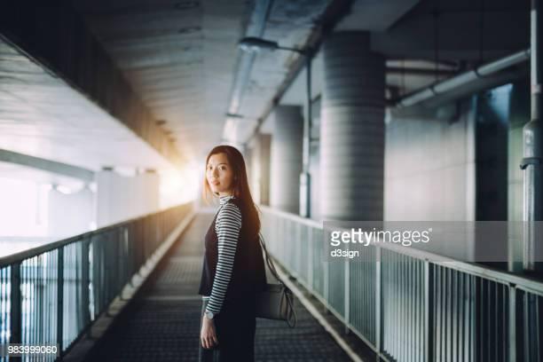 young woman looking over shoulder while walking alone in urban bridge in city - mirar por encima del hombro fotografías e imágenes de stock