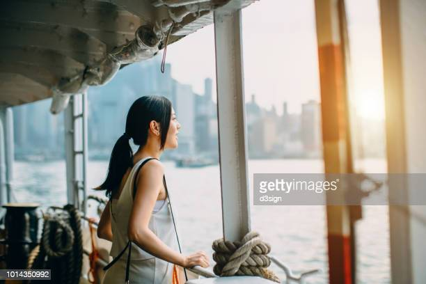 young woman looking over the spectacular city skyline of hong kong at dusk while riding on star ferry - star ferry stock photos and pictures