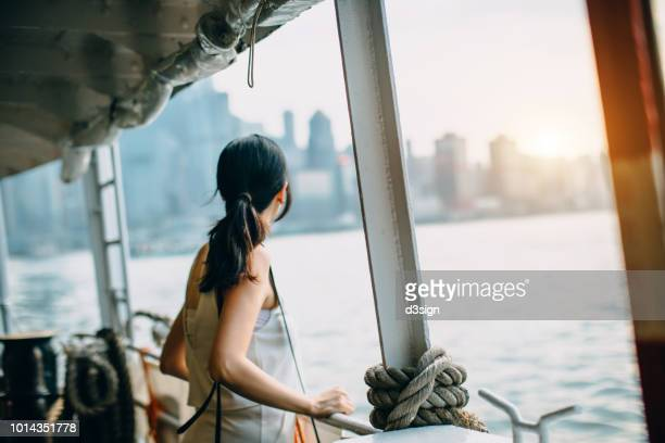 young woman looking over the spectacular city skyline of hong kong at dusk while riding on star ferry - ferry stock pictures, royalty-free photos & images