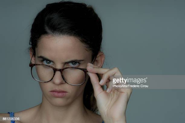Young woman looking over the top of her eyeglasses, frowning, portrait