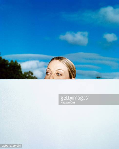 Young woman looking over wall outdoors, high section