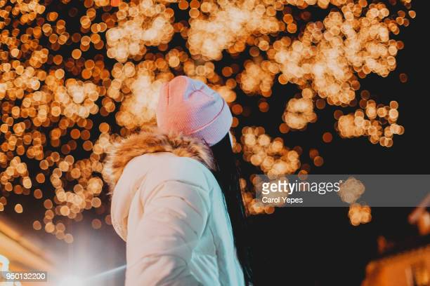 young woman looking the fireworks in the sky - happy new month - fotografias e filmes do acervo