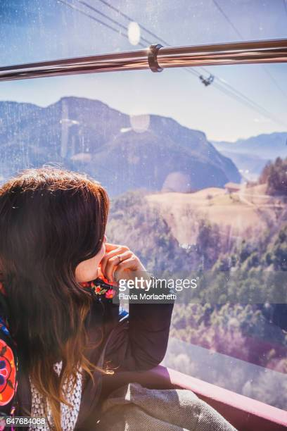 Young woman looking thought cable car window