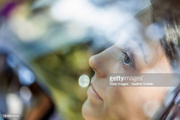 A young woman looking thoughtfully out the window of a stationary car