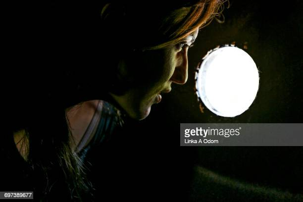 Young woman looking through a keyhole