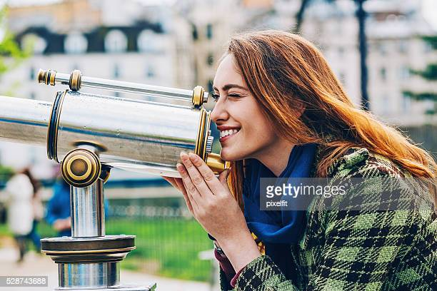 Young woman looking through a telescope in Paris city