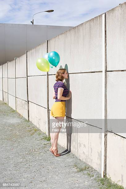 young woman looking through a wall
