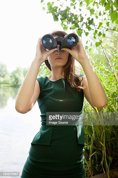 Young woman looking through binoculars by a lake