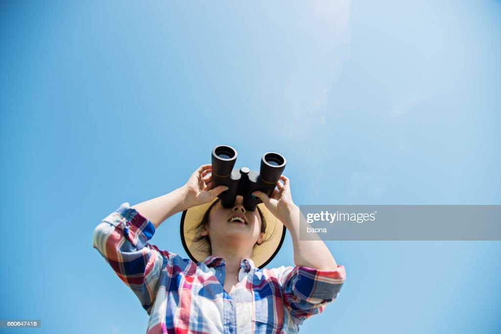 Young woman looking through binoculars : Stock Photo