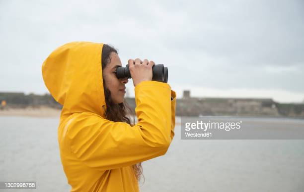 young woman looking through binoculars while standing at beach - binoculars stock pictures, royalty-free photos & images