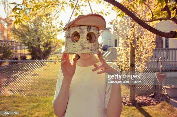 Young Woman Looking Through Bird House At Park