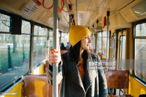 young woman looking through bus window - tram stockfoto's en -beelden