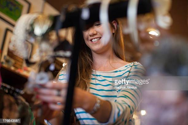 Young woman looking through clothes rail in vintage shop