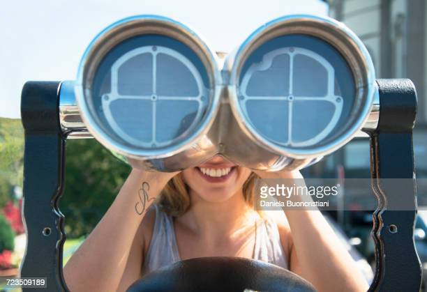 Young woman looking through coin operated binoculars at the Monte dei Cappuccini, Turin, Italy