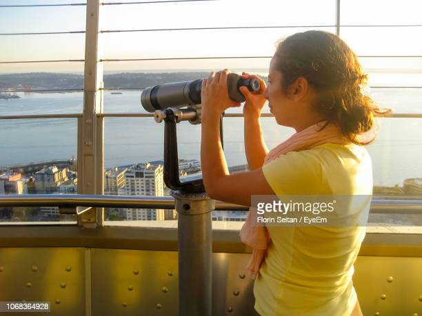 young woman looking through coin-operated binoculars by river - florin seitan stock pictures, royalty-free photos & images