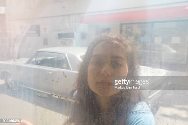 Young woman looking through dirty window
