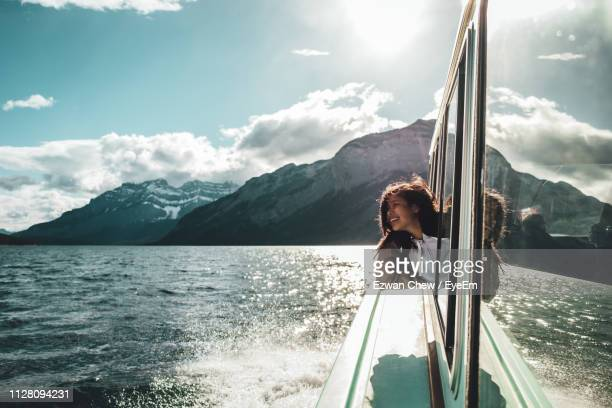 young woman looking through ferry boat window in sea - fähre stock-fotos und bilder
