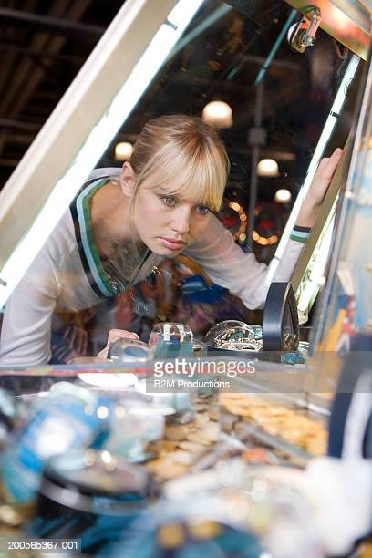 Young woman looking through glass at toy grabbing game