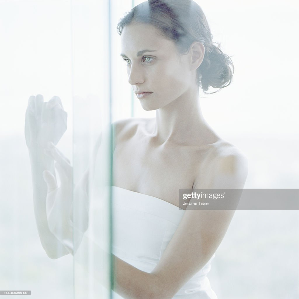 Young Woman Looking Through Glass Door In Bathroom Stock Photo
