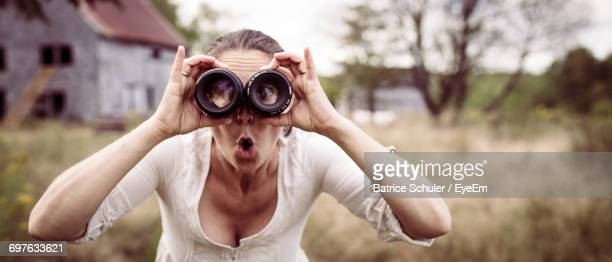 Young Woman Looking Through Lenses