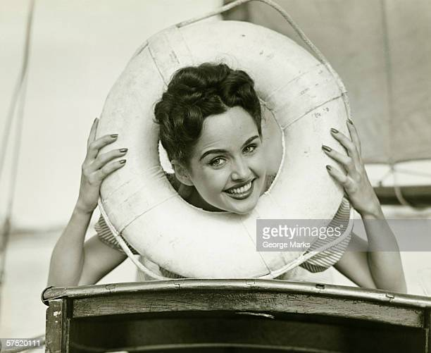 young woman looking through lifebelt, smiling, (b&w) - permed hair stock pictures, royalty-free photos & images