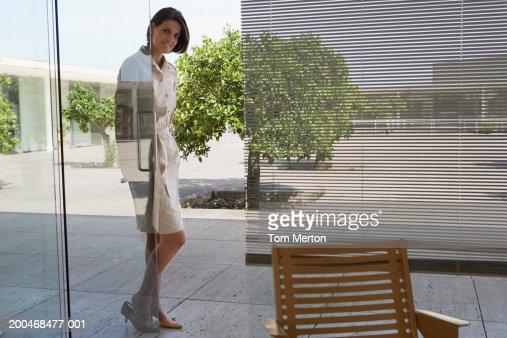 Young Woman Looking Through Open Glass Door Smiling Portrait Stock