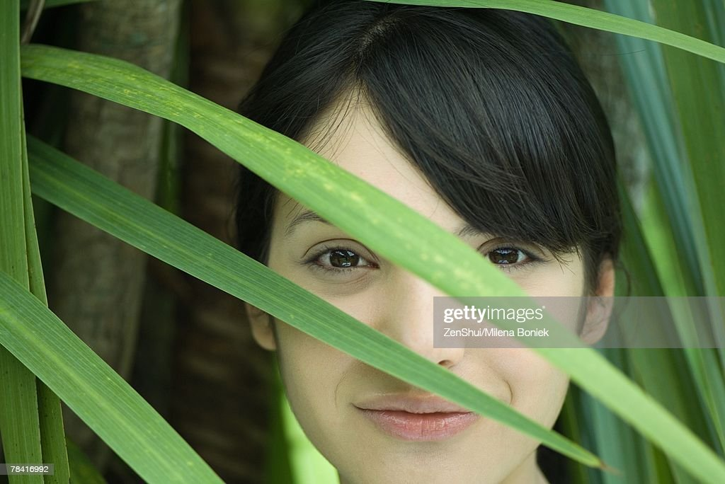 Young woman looking through palm leaf, smiling at camera, portrait : Stock Photo