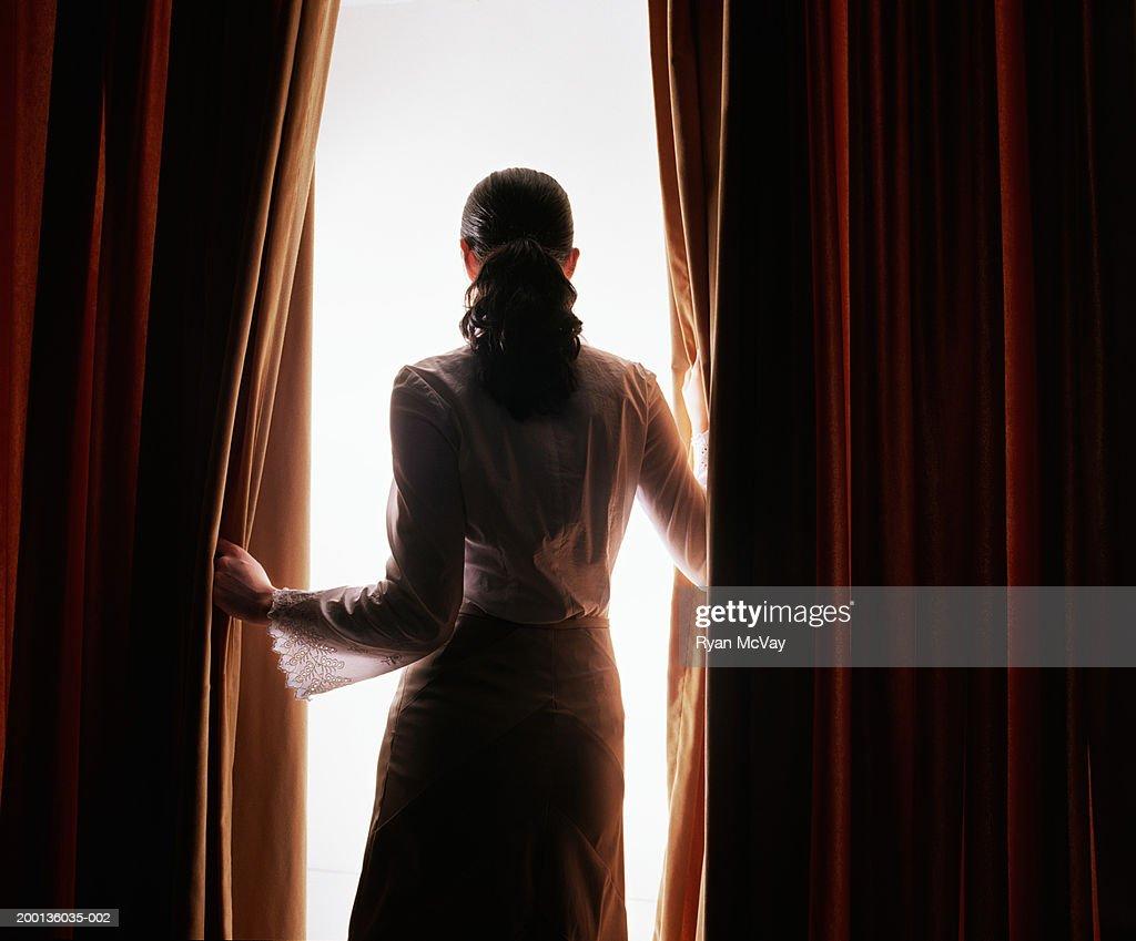 Joven mujer mirando a través de la red y cortinas oscurecedoras (black out), Vista posterior : Foto de stock
