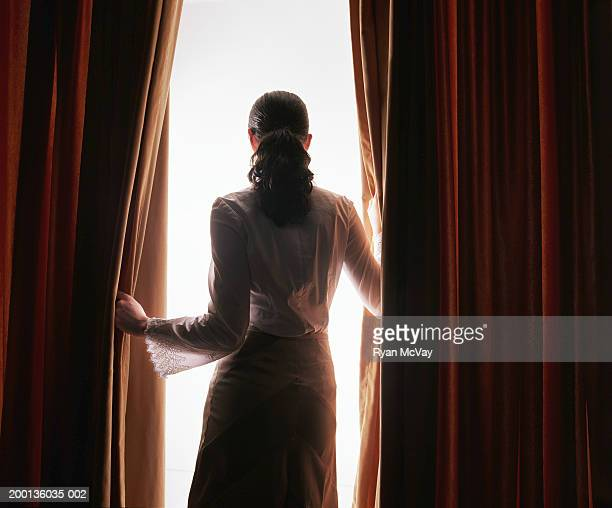 young woman looking through red curtains, rear view - mystery stock pictures, royalty-free photos & images