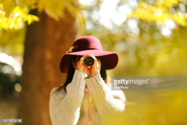 Young woman looking through telescope in autumn park