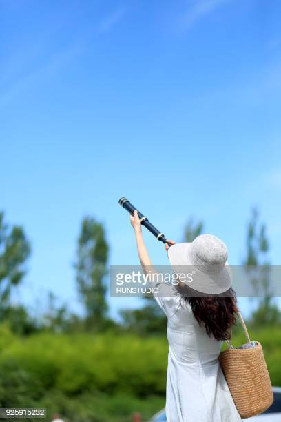 Young woman  looking through telescope outdoors
