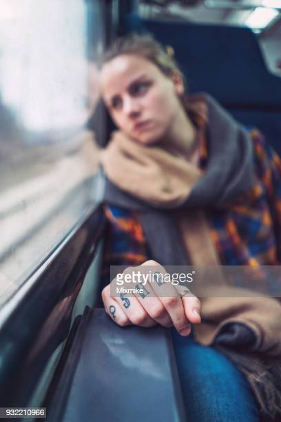 Young woman looking through the train window while travelling