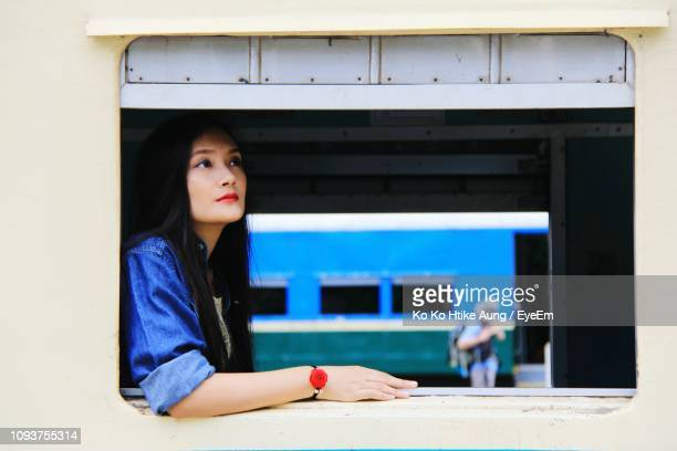 young woman looking through train window - ko ko htike aung stock pictures, royalty-free photos & images