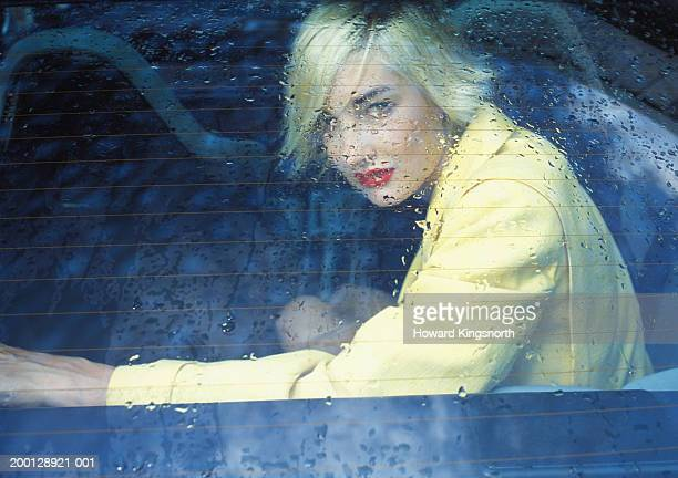 Young woman looking through wet rear windscreen, portrait