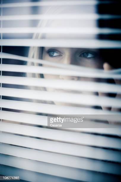 Young Woman Looking Through Window Blinds